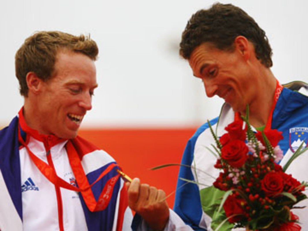 Vasilij Zbogar (R) of Slovenia checks the gold medal of winner Paul Goodison (L) of Great Britain at the Beijing Olympic Games